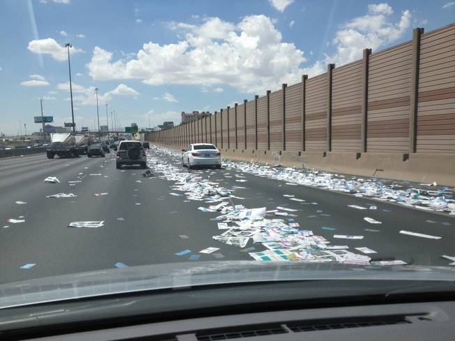 Papers litters Interstate 15 between Sahara Avenue and Charleston Boulevard after a box fell from a truck and was hit by a bus Tuesday, July 24, 2012.