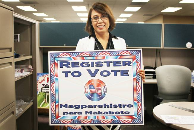 "May Manahan, elections operations specialist for Clark County, holds a sign that reads ""register to vote"" in English and Filipino. In October the federal government informed the county that, based on demographic data, elections materials must be translated into Filipino."
