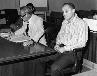 UNLV basketball coach Jerry Tarkanian, right, awaits proceedings in district court Thursday, Sept. 7, 1977, as his lawyer Samuel Lionel prepares for a hearing to block the university's bid to remove Tarkanian from his position in compliance with an NCAA ultimatum.