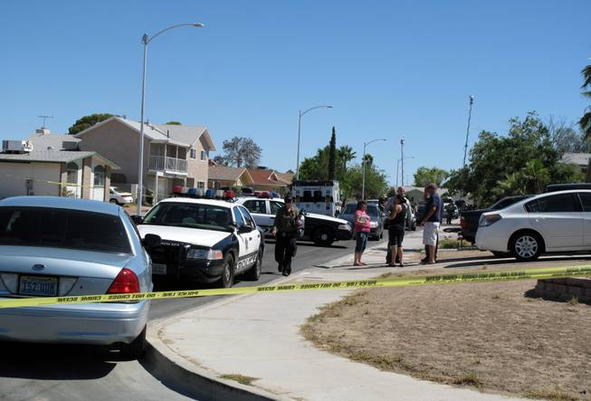Metro Police cars swarm a western valley house in the aftermath of a shooting Friday, July 27, 2012. The shooting in a home in the 300 block of Altamira Road claimed the life of a woman and left a man in stable condition at University Medical Center.