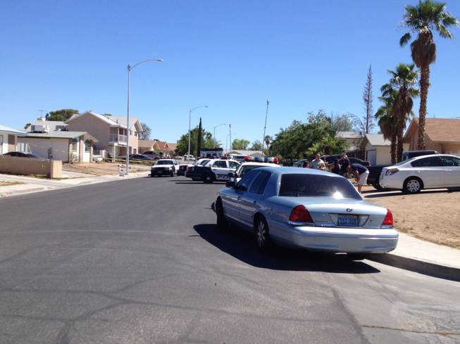 Metro Police cars swarm a western valley house in the aftermath of a shooting Friday, July 27, 2012. The shooting in a home in the 300 block of Altamira Road claimed the life of a woman and left a man in stable condition at University Medical Center. Police continue to search for the shooter.