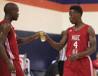 Marcus Allen hands his brother Malcolm Allen a drink at the Fab 48 tournament Friday, July 27, 2012, at Bishop Gorman.