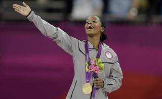 U.S. gymnast Gabrielle Douglas acknowledges the crowd after receiving her gold medal during the artistic gymnastics women's individual all-around competition at the 2012 Summer Olympics, Thursday, Aug. 2, 2012, in London.