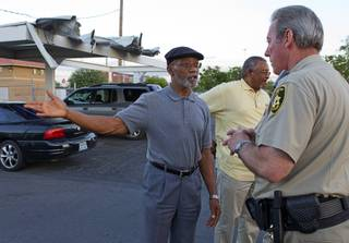 Mujahid Ramadan, left, talks with Metro Police Capt. Larry Burns at the Desert Gardens Condominiums complex near Martin Luther King Jr. Boulevard and Bonanza Road Monday, Aug. 6, 2012. Pastor Willie Cherry is in the background.