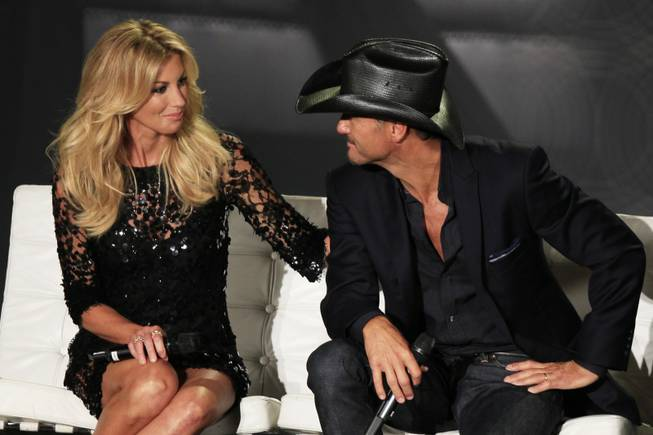 Faith Hill and Tim McGraw look at each other while deciding how to answer a question after announcing their concert series at the Venetian on Tuesday, Aug. 7, 2012.