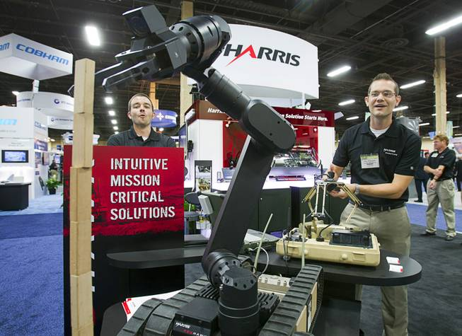 Paul Bosscher, right, of the Harris Corporation, reacts after stacking 10 jenga blocks - tieing the company record - using the Harris Redhawk robotic arm control system during the Association for Unmanned Vehicles Systems International (AUVSI) convention at the Mandalay Bay Thursday, Aug. 9, 2012. The wireless system gives operators tactile feedback for precision manipulation.
