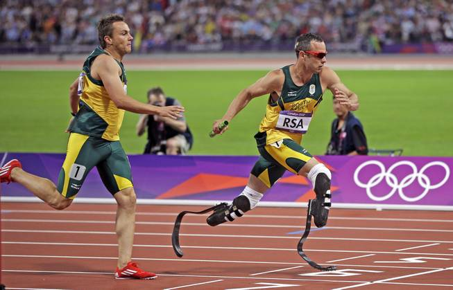 South Africa's Oscar Pistorius takes the baton from teammate L.J. van Zyl during the men's 4x400-meter in Olympic Stadium at the 2012 Summer Olympics, London, Aug. 10, 2012.
