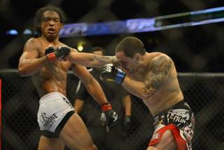 Benson Henderson from Arizona, left takes a right to the chin from Frankie Edgar from New Jersey in their middleweight title bout during UFC 150 in Denver, Saturday, Aug. 11, 2012. Henderson won the bout.