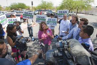 U.S. Congresswoman Shelley Berkley (D-NV) holds a  news conference in the parking lot of Palo Verde High School before a rally for Republican vice presidential candidate Paul Ryan at the school Tuesday, Aug. 14, 2012. Berkley is running for U.S. Senate against Sen. Dean Heller (R-NV). Heller supporters hold up signs in the background.