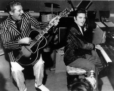 Piano virtuoso Liberace is shown playing the guitar with Elvis Presley at the piano in November 1956 at the Riviera Hotel in Las Vegas.
