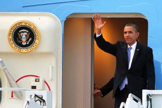 President Barack Obama waves as he departs Air Force One after arriving at Nellis Air Force Base northeast of Las Vegas on Tuesday, August 21, 2012.