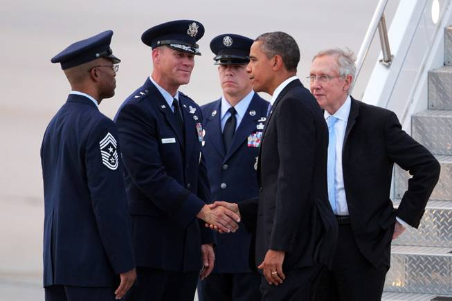 President Barack Obama, Sen. Harry Reid, D-Nev., greets Chief Master Sgt. Robert Ellis, Commander Chief of the U.S. Air Force Warfare Center at Nellis, from left, and General Jeffrey Lofgren, Commander at the U.S. Air Force Warfare Center at Nellis, after arriving at Nellis Air Force Base northeast of Las Vegas on Tuesday, August 21, 2012.
