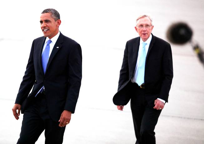 President Barack Obama and Sen. Harry Reid, D-Nev. walk on the tarmac after arriving at Nellis Air Force Base northeast of Las Vegas on Tuesday, August 21, 2012.