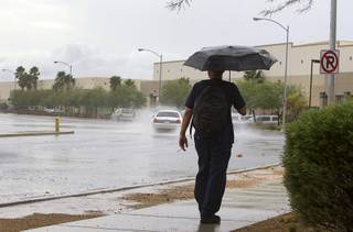 A man walks in the rain on North Pecos Road in North Las Vegas Wednesday, Aug. 22, 2012.