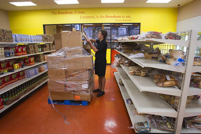 Volunteer Chason Borges helps stock shelves at the Agency Store at the Three Square Food Bank Wednesday, Aug. 22, 2012.