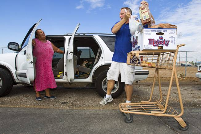 Tony Voggetzer, of Sunrise Baptist Church, loads food into an SUV for Connie Diemoz, left, at the church Thursday, Aug. 23, 2012.