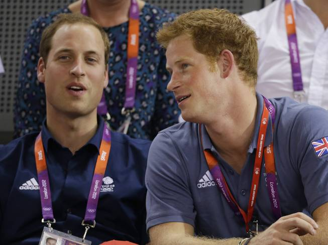 Britain's Prince William, left, and Prince Harry talk while watching track cycling at the velodrome during the 2012 Summer Olympics, Thursday, Aug. 2, 2012, in London.