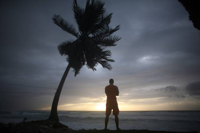 A man looks out at the beach as Tropical Storm Isaac approaches in Barahona, Dominican Republic, Friday, Aug. 24, 2012. Fears over the storm have forced the GOP to cancel Monday evening's events at the Republican National Convention in Tampa, Fla.