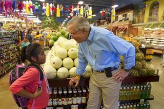 Senate Majority Leader Harry Reid talks with second grader Noemi Ramirez while touring Cardenas  Market at Meadows Lane and Decatur Boulevard Monday, Aug. 27, 2012.