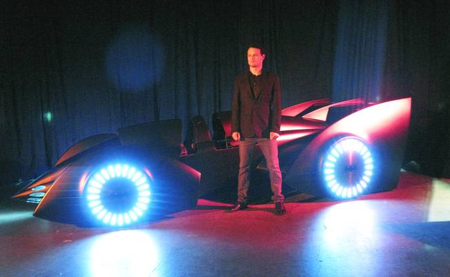 "Actor Sam Heughan poses with a new version of the Batmobile that was unveiled at the UNLV Cox Pavillion in Las Vegas on Monday in advance of the arrival of ""Batman Live"" in October. Heughan stars as Batman in ""Batman Live"", a stage production that combines the classic story of the comic book super hero with high-flying acrobatics, pyrotechnics and an original score."