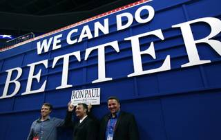 Nevada delegate and former state Ron Paul campaign chair Carl Bunce, right, and Nevada delegate David Isbell, center, help hold up a Ron Paul sign under Mitt Romney's