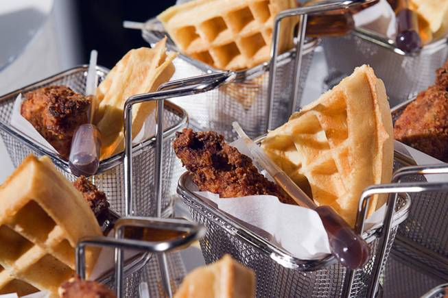 Baskets of fried chicken and waffles with syrup dispensers are ...