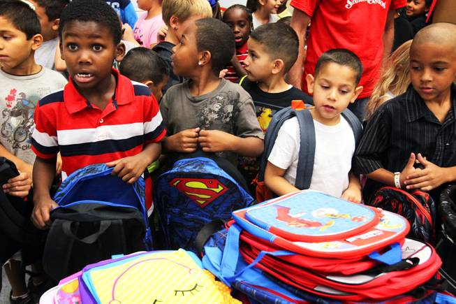 "Students from Whitney Elementary School grab free backpacks donated by Station Casinos at the school on Wednesday, August 29, 2012. The donation was part of Station Casinos ""Smart Start"" school sponsorship program to assist high need elementary schools in the Las Vegas Valley."