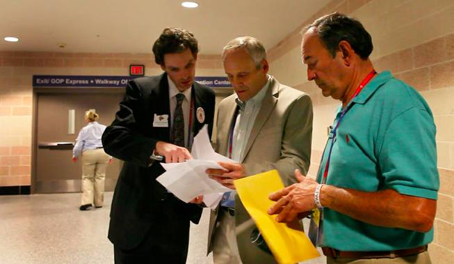 Nevada delegation chair Wayne Terhune discusses a petition to enter Ron Paul's name on the ballot with delegates in the hallway off the convention floor Tuesday afternoon, Aug. 28, 2012.