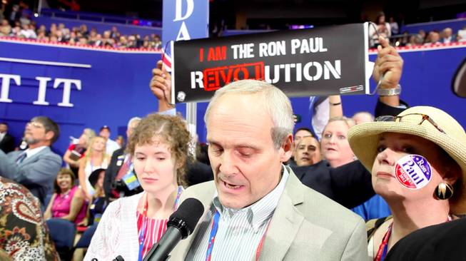 Nevada delegation chair Wayne Terhune announces the Nevada delegates' vote for Ron Paul on the floor of the RNC Tuesday evening, as members of the delegation display Ron Paul emblems and paraphernalia they snuck into the convention hall, Aug. 28, 2012.