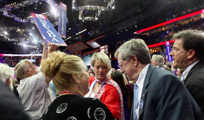 Washoe County GOP chairman Dave Buell wrests the Nevada delegation's state sign off its pole, being held by Nevada delegate Kim Bacchus, after the close of the Republican National Convention Thursday night Aug. 30, 2012 in Tampa, as National Committeewoman Heidi Smith, National Committeeman Bob List and Lieutenant Governor Brian Krolicki look on.