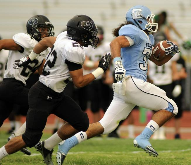 Centennial runningback Coby Newton evades Palo Verde tacklers Calvin Beaulieu (22) and  Ryan Beaulieu (24) during second quarter action at Centennial High School on Friday evening.