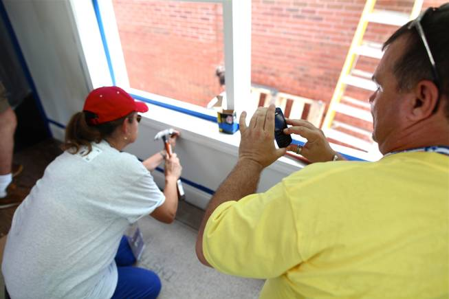 Linda Cavazos, a Nevada delegate and an Organizing for America volunteer, hammers a nail into a window frame while Clark County Democratic Party chairman Chris Miller snaps a picture on his phone.