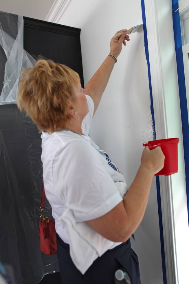 Elizabeth Foyt, an alternate delegate, paints a wall in the modular home Nevada volunteers and others worked on Monday morning.