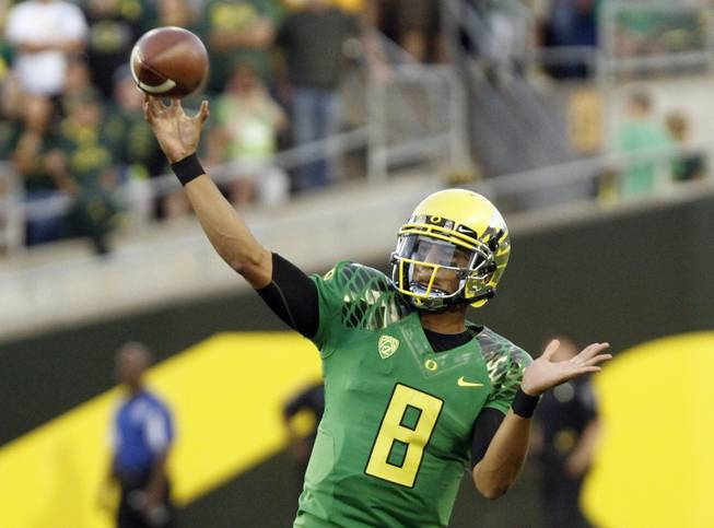Oregon quarterback Marcus Mariota passes the ball downfield in the first half of a game against Arkansas State. Oregon went on to 57-34.