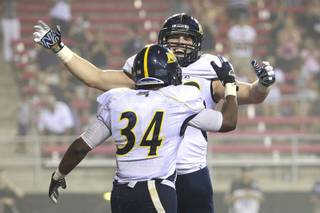 Northern Arizona lineman Trey Gilleo rushes to greet running back Zach Bauman after Bauman's touchdown during their game Saturday, Sept. 8, 2012 at Sam Boyd Stadium. The Division I-AA Lumberjacks upset the Rebels 17-14.