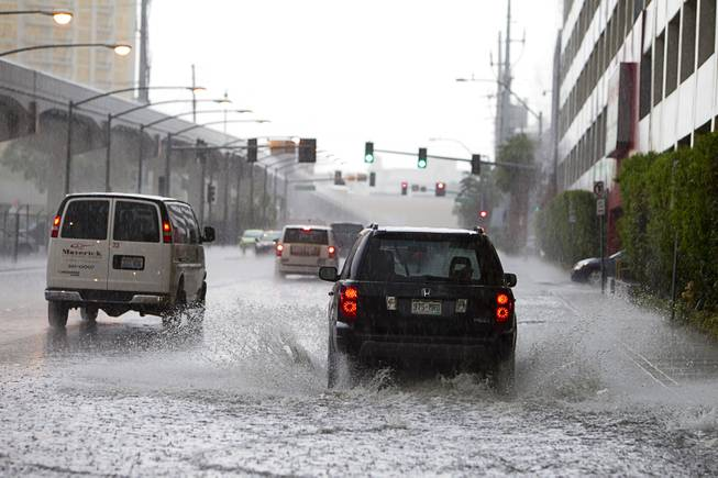 Cars drive through storm runoff behind Planet Hollywood during a rainstorm Tuesday, Sept. 11, 2012.