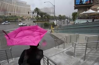Wind turns a woman's umbrella inside out in front of Planet Hollywood during a rainstorm Tuesday, Sept. 11, 2012.