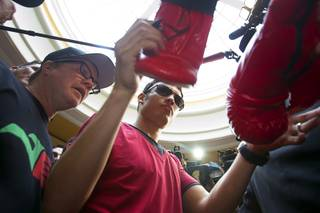 WBC middleweight champion Julio Cesar Chavez Jr. of Mexico, son of boxing legend Julio Cesar Chavez, signs boxing gloves as he arrives at the Wynn Tuesday, Sept. 11, 2012. Trainer Freddie Roach looks on at left. Chavez will defend his title against Sergio Martinez of Argentina at the Thomas & Mack Arena on Saturday.