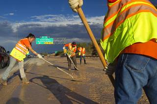 A Nevada Department of Transportation crew works to clear the roadway at the I-215 eastbound off-ramp to the airport connector Tuesday, Sept. 11, 2012. Run off from heavy rains filled the roadway with mud and debris.