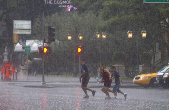A family crosses Las Vegas Boulevard in front of the Bellagio during a rainstorm Tuesday, Sept. 11, 2012.