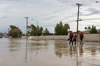 Las Vegas Firefighters escort a man out of the flooded intersection of E. Sahara Avenue and Winterwood Boulevard after his vehicle became stranded, Tuesday, Sept. 11, 2012.