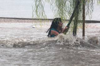 A Knudson Middle School student hangs onto a tree after falling down and being dragged by  floodwater near Eastern and Sahara avenues, Sept. 11, 2012.