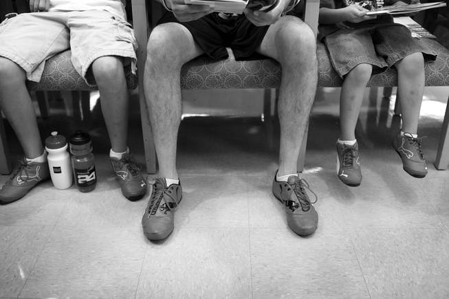 Arturo Martinez-Sanchez, center, sits in the Valley Hospital waiting room with his sons Cristopher, left, 10, and Alejandro, 5, all in matching shoes on the day of Arturo's brain surgery Sept. 12, 2012.