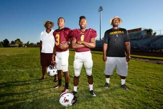 The Brown family, from left, Vernon Brown Sr., Sundevil quarterback Joshua Brown, Sundevil running back Justin Brown and head coach Vernon Brown stand together for their three-generation love of football at Eldorado High School Wednesday, September 13, 2012.