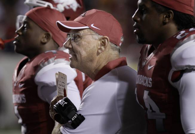 Arkansas coach John L. Smith, center, watches a college football game against Louisiana-Monroe with cornerback Kelvin Fisher, left, and linebacker Daunte Carr during the fourth quarter in Little Rock, Ark. After the loss to the Warhawks, the pressure is on Smith as the suddenly unranked Razorbacks prepare for No. 1 Alabama.
