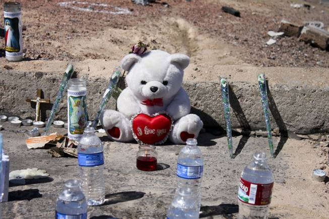 Open water bottles are seen along with other mementoes at the memorial site of the bus stop crash Friday, Sept. 14, 2012.