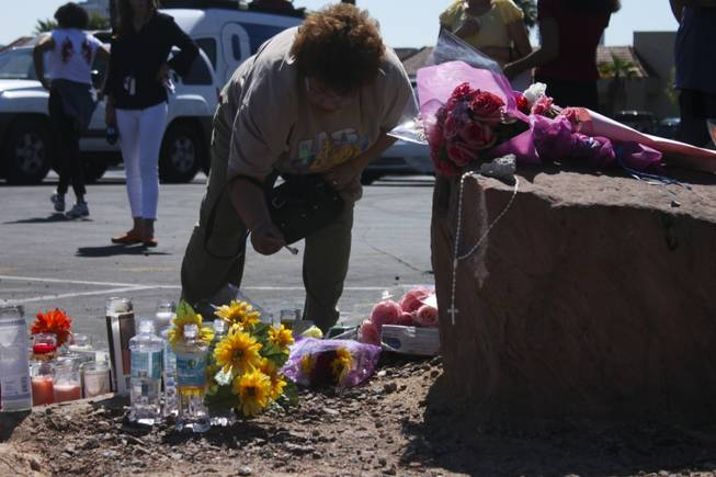 Cecilia Mendez, co-worker of one of the victims, lights a candle at the memorial site of the bus stop crash Friday, Sept. 14, 2012.