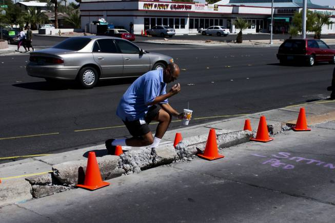 Deacon Andre Richard from the Roman Catholic Diocese of Las Vegas says a prayer at the memorial site of the bus stop crash, Friday, Sept. 14, 2012.