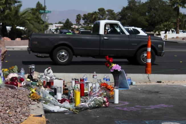 A child looks out onto the memorial site of the bus stop crash from the passenger side of a passing truck Friday, Sept. 14, 2012.
