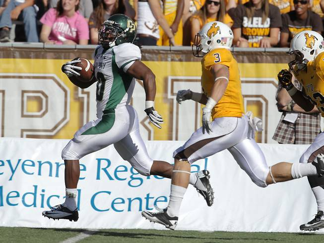 Cal Poly running back Deonte Williams (left) runs away from Wyoming defender Luke Anderson in Cal Poly's 24-22 victory on Saturday, Sept. 15, 2012, in Laramie, Wyo.